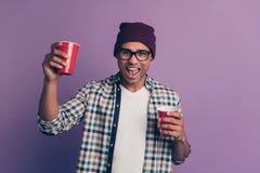 Ritratto della foto del tipo funky pazzo che gode del fine settimana di festa che giudica alzando vetro di plastica con la bevand fotografia stock