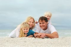Ritratto della gente felice di famiglia di quattro che si rilassa sulla spiaggia Fotografia Stock Libera da Diritti