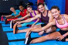 Ritratto della gente sorridente che fa allungando esercizio in palestra Fotografia Stock