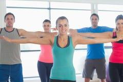 Ritratto della gente sportiva che allunga fuori le mani alla classe di yoga Fotografia Stock
