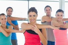 Ritratto della gente sportiva che allunga le mani alla classe di yoga Immagini Stock