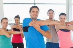 Ritratto della gente sportiva che allunga le mani alla classe di yoga Immagine Stock Libera da Diritti