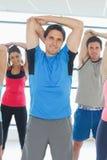 Ritratto della gente sportiva che allunga le mani alla classe di yoga Fotografia Stock Libera da Diritti