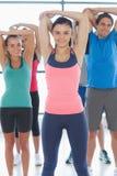 Ritratto della gente sportiva che allunga le mani alla classe di yoga Fotografie Stock