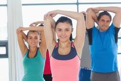 Ritratto della gente sportiva che allunga le mani alla classe di yoga Immagine Stock