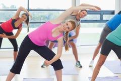 Ritratto della gente sportiva che allunga le mani alla classe di yoga Fotografia Stock