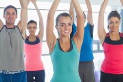 Ritratto della gente sportiva che allunga sulle mani alla classe di yoga Immagini Stock