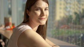 Ritratto della giovane donna abbastanza vaga che si siede alla tavola in caffè vicino al pensiero della finestra Centro commercia video d archivio