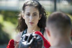 Ritratto della giovane donna in abiti sportivi all'allenamento di pugilato nel parco di estate Fotografia Stock Libera da Diritti