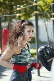 Ritratto della giovane donna in abiti sportivi all'allenamento di pugilato nel parco di estate Fotografia Stock