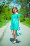 Ritratto della giovane donna alla moda della testarossa nel parco di primavera fotografie stock