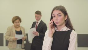 Ritratto della giovane donna attraente adorabile nell'usura convenzionale che parla dal cellulare nella priorità alta nell'attimo stock footage