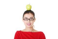 Ritratto della giovane donna attraente con la mela sulla testa. Fotografia Stock