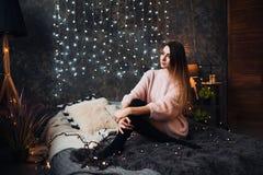 Ritratto della giovane donna attraente triste con i coriandoli del lamé e le luci della ghirlanda che celebra la stanza scura del immagine stock libera da diritti