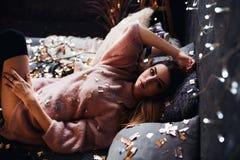 Ritratto della giovane donna attraente triste con i coriandoli del lamé e le luci della ghirlanda che celebra la stanza scura del fotografie stock