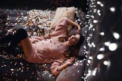 Ritratto della giovane donna attraente triste con i coriandoli del lamé e le luci della ghirlanda che celebra la stanza scura del immagini stock