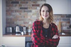 Ritratto della giovane donna in camicia rossa alla cucina immagini stock libere da diritti