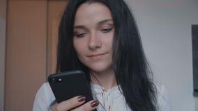 Ritratto della giovane donna castana facendo uso dello smartphone a casa video d archivio