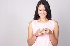 Ritratto della giovane donna caucasica che per mezzo di un telefono cellulare Fotografia Stock Libera da Diritti