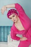Ritratto della giovane donna che allunga mentre stando sul letto Immagini Stock Libere da Diritti