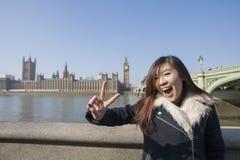 Ritratto della giovane donna che gesturing V-segno contro Big Ben a Londra, Inghilterra, Regno Unito Fotografie Stock