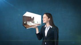 Ritratto della giovane donna che giudica 3d interno sulla palma aperta della mano, sopra il fondo isolato dello studio Concetto d Fotografie Stock