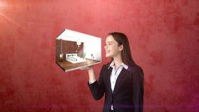 Ritratto della giovane donna che giudica 3d interno sulla palma aperta della mano, sopra il fondo isolato dello studio Concetto d Immagini Stock Libere da Diritti