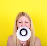 Ritratto della giovane donna che grida con un megafono contro il giallo Fotografie Stock