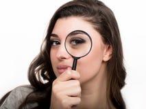 Ritratto della giovane donna che guarda tramite la lente d'ingrandimento Fotografia Stock