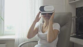 Ritratto della giovane donna che guarda video 360 in cuffia avricolare di realtà virtuale a casa Metraggio sparato a 4K video d archivio