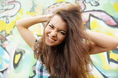 Ritratto della giovane donna che si siede alla parete dei graffiti Fotografia Stock Libera da Diritti