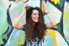 Ritratto della giovane donna che si siede alla parete dei graffiti Immagine Stock Libera da Diritti