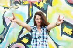 Ritratto della giovane donna che si siede alla parete dei graffiti Immagini Stock