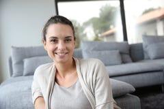 Ritratto della giovane donna che si siede a casa Fotografia Stock