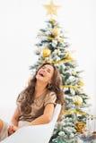 Ritratto della giovane donna che si siede vicino all'albero di Natale ed alla risata immagine stock libera da diritti