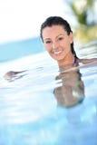 Ritratto della giovane donna che sorride che si rilassa nella piscina Fotografie Stock