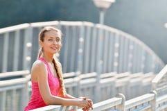 Ritratto della giovane donna che sorride sul ponte urbano della città del metallo dopo l'allenamento corrente Immagini Stock