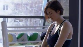 Ritratto della giovane donna, che sta facendo gli esercizi di riscaldamento in palestra moderna archivi video