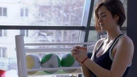 Ritratto della giovane donna che sta facendo i exersices di riscaldamento dalle sue mani nell'addestramento moderno del berofe de stock footage