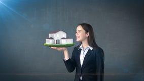 Ritratto della giovane donna che tiene casa moderna sulla palma aperta della mano, sopra il fondo isolato dello studio Concetto d Fotografia Stock