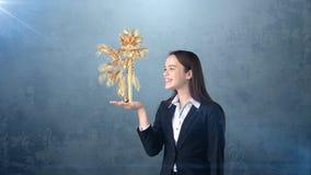 Ritratto della giovane donna che tiene palma dorata sulla palma aperta della mano, sopra il fondo isolato dello studio Concetto d Fotografie Stock Libere da Diritti