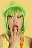Ritratto della giovane donna colpita con capelli verdi contro fondo giallo Immagini Stock Libere da Diritti
