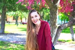 Ritratto della giovane donna con capelli lunghi che sorride sulla macchina fotografica davanti a Sakura Fotografie Stock