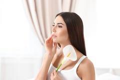 Ritratto della giovane donna con il fiore della calla Cura del corpo e di bellezza fotografie stock libere da diritti