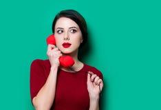 Ritratto della giovane donna con il microtelefono rosso fotografia stock
