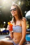 Ritratto della giovane donna con il vetro di cocktail che raffredda nel sole tropicale vicino alla piscina su uno sdraio con la p fotografie stock