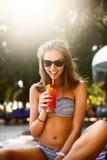 Ritratto della giovane donna con il vetro di cocktail che raffredda nel sole tropicale vicino alla piscina su uno sdraio con la p fotografie stock libere da diritti