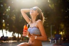 Ritratto della giovane donna con il vetro di cocktail che raffredda nel sole tropicale vicino alla piscina su uno sdraio con la p fotografia stock libera da diritti