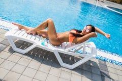 Ritratto della giovane donna con il vetro di cocktail che raffredda nel sole tropicale vicino alla piscina su uno sdraio Concetto Fotografia Stock