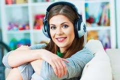 Ritratto della giovane donna con l'ascolto di musica delle cuffie Immagine Stock